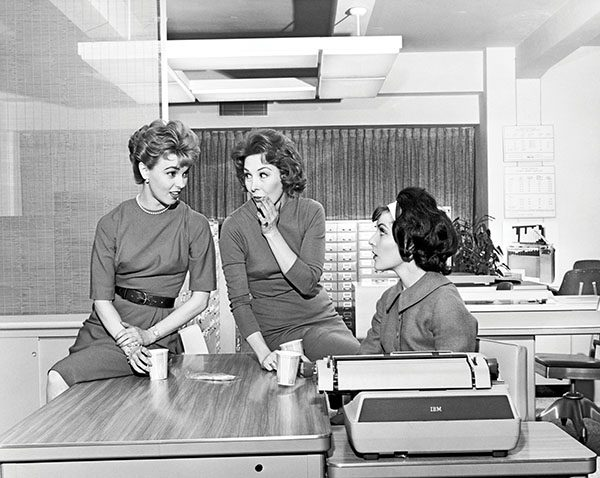 Three businesswomen gossiping in an office